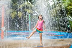 Kids play in aqua park. Children at water playground of tropical amusement park. Little girl at swimming pool. Child playing at. Water slide on summer vacation royalty free stock photo