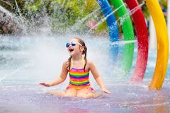 Kids at aqua park. Child in swimming pool. Kids play in aqua park. Children at water playground of tropical amusement park. Little girl at swimming pool. Child royalty free stock photos
