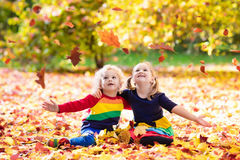 Kids play in autumn park. Children in fall. Kids play in autumn park. Children throwing yellow maple leaves. Boy and girl jump and run with oak leaf. Fall Royalty Free Stock Photos