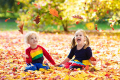 Kids play in autumn park. Children in fall. Kids play in autumn park. Children throwing yellow maple leaves. Boy and girl jump and run with oak leaf. Fall Stock Photos