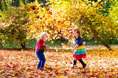 Kids play in autumn park. Children in fall. Kids play in autumn park. Children throwing yellow maple leaves. Boy and girl jump and run with oak leaf. Fall Stock Photo