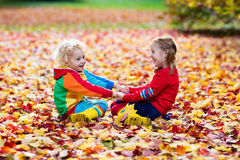Kids play in autumn park. Children in fall. Kids play in autumn park. Children throwing yellow maple leaves. Boy and girl jump and run with oak leaf. Fall Stock Images
