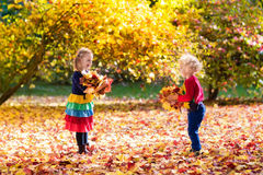 Kids play in autumn park. Children in fall. Kids play in autumn park. Children throwing yellow maple leaves. Boy and girl jump and run with oak leaf. Fall Royalty Free Stock Photo