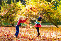 Kids play in autumn park. Children in fall. Kids play in autumn park. Children throwing yellow maple leaves. Boy and girl jump and run with oak leaf. Fall Stock Image