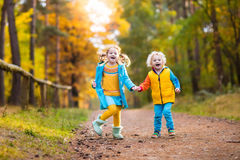 Kids play in autumn park. Children in fall. Kids play in autumn park. Children throwing yellow maple leaves. Boy and girl jump and run with oak leaf. Fall Royalty Free Stock Photography