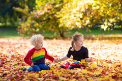 Kids play in autumn park. Children in fall. Kids play in autumn park. Children throwing yellow maple leaves. Boy and girl jump and run with oak leaf. Fall Stock Photography
