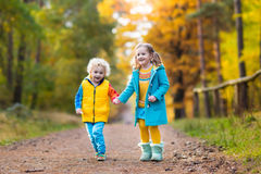 Kids play in autumn park. Children in fall. Kids play in autumn park. Children throwing yellow maple leaves. Boy and girl jump and run with oak leaf. Fall Royalty Free Stock Image