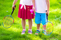 Kids play badminton or tennis in outdoor court Stock Photography
