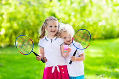 Kids play badminton or tennis in outdoor court. Active preschool girl and boy playing badminton in outdoor court in summer. Kids play tennis. School sports for stock image