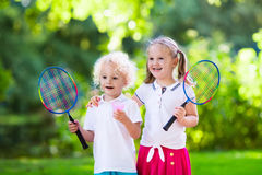 Kids play badminton or tennis in outdoor court. Active preschool girl and boy playing badminton in outdoor court in summer. Kids play tennis. School sports for stock photos