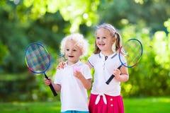 Kids play badminton or tennis in outdoor court Stock Photos