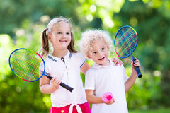 Kids play badminton or tennis in outdoor court. Active preschool girl and boy playing badminton in outdoor court in summer. Kids play tennis. School sports for stock photo