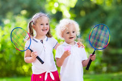 Kids play badminton or tennis in outdoor court. Active preschool girl and boy playing badminton in outdoor court in summer. Kids play tennis. School sports for stock photography