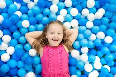Kids play in ball pit. Child playing in balls pool. Child playing in ball pit. Colorful toys for kids. Kindergarten or preschool play room. Toddler kid at day Royalty Free Stock Images
