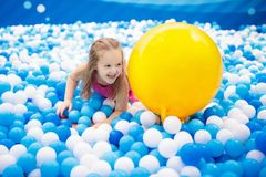 Kids play in ball pit. Child playing in balls pool. Child playing in ball pit. Colorful toys for kids. Kindergarten or preschool play room. Toddler kid at day Stock Photos