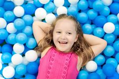 Kids play in ball pit. Child playing in balls pool. Child playing in ball pit. Colorful toys for kids. Kindergarten or preschool play room. Toddler kid at day Stock Image