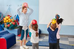 Kids play with balls in gym. Children play with balls in the gym together with kindergarten teacher or sports teacher royalty free stock image