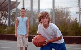 Kids play basketball in a school. Teenagers play basketball in a school stock images