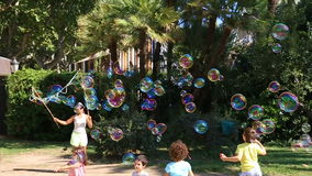Kids play with bubbles. Lots of bubbles in the park in Barcelona, Spain on August 23, 2015 stock footage