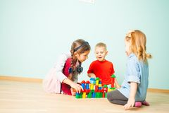 Kids play at day care. Three preschoolers building tower from wooden cubes stock photos