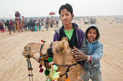 Kids play with domestic camel in the valley. JAISALMER, INDIA: Kids play with domestic camel in the valley during the popular annual Desert Festivalin Rajasthan stock photos