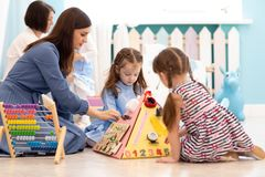 Kids play with educational toy in nursery royalty free stock images