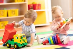 Kids play with educational toys. Children sit on a rug in a play room at home or kindergarten. Toddler boy with toy stock photography