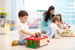 Kids play with educational toys, educator looking after pupils in kindergarten stock photography
