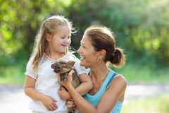 Kids and farm animals. Child with baby pig at zoo. Kids play with farm animals. Child feeding domestic animal. Young mother and little girl holding wild boar stock photography