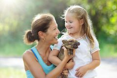 Kids and farm animals. Child with baby pig at zoo. Kids play with farm animals. Child feeding domestic animal. Young mother and little girl holding wild boar royalty free stock image
