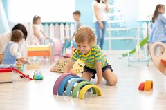 Kids play on floor with educational toys. Toys for preschool and kindergarten. Children in nursery or daycare