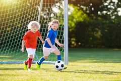Kids play football. Child at soccer field. Kids play football on outdoor field. Children score a goal at soccer game. Girl and boy kicking ball. Running child stock photo