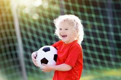 Kids play football. Child at soccer field. Kids play football on outdoor field. Children score a goal at soccer game. Little boy kicking ball. Running child in Royalty Free Stock Image