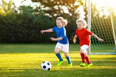 Kids play football. Child at soccer field. Kids play football on outdoor field. Children score a goal at soccer game. Girl and boy kicking ball. Running child stock photography