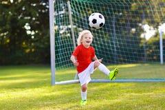 Kids play football. Child at soccer field. Kids play football on outdoor field. Children score a goal during soccer game. Little boy kicking ball. Running child stock photo