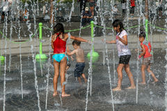 Kids play in fountain. New York, August 10, 2017: Kids are getting soaking wet while playing with a fountain during a hot summer day royalty free stock image