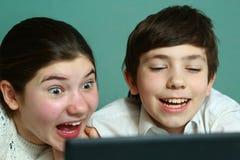 Kids play game in laptop, laughing Royalty Free Stock Photo