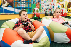 Kids play in a games console, happy childhood. Smiling kids play in a games console in childrens entertainment center. Happy childhood Stock Photo