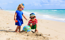 Kids play with globe and toy plane on beach, travel concept Stock Photos