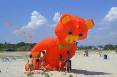 Kids play with huge orange bear kite Royalty Free Stock Photos