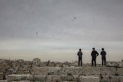 Kids play with kites. AMMAN, JORDAN - MARCH 12, 2019: Three children play with home-made kites on the walls of the ancient citadel of Amman, with the old city in royalty free stock image