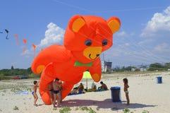 Kids play with orange bear kite Royalty Free Stock Image