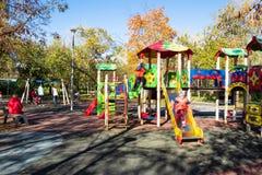Kids play on outdoor playground in public garden stock photo