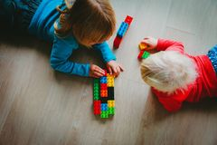 Kids play with plastic blocks, learning concept stock photography