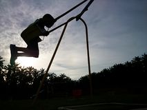 Kids play at playground. Sunset and silhouette Royalty Free Stock Photo