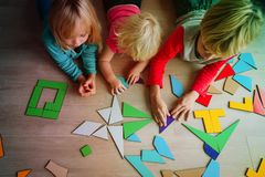 Kids play with puzzle, learn math, education concept. Kids playing with puzzle, education and learning concept stock photography