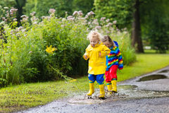 Kids play in rain and puddle in autumn. Little boy and girl play in rainy summer park. Children with colorful rainbow jacket and waterproof boots jump in puddle Royalty Free Stock Photos