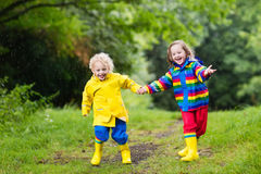 Kids play in rain and puddle in autumn Stock Image