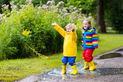 Kids play in rain and puddle in autumn Royalty Free Stock Images
