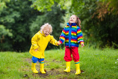 Kids play in rain and puddle in autumn. Little boy and girl play in rainy summer park. Children with colorful rainbow jacket and waterproof boots jump in puddle Stock Photos